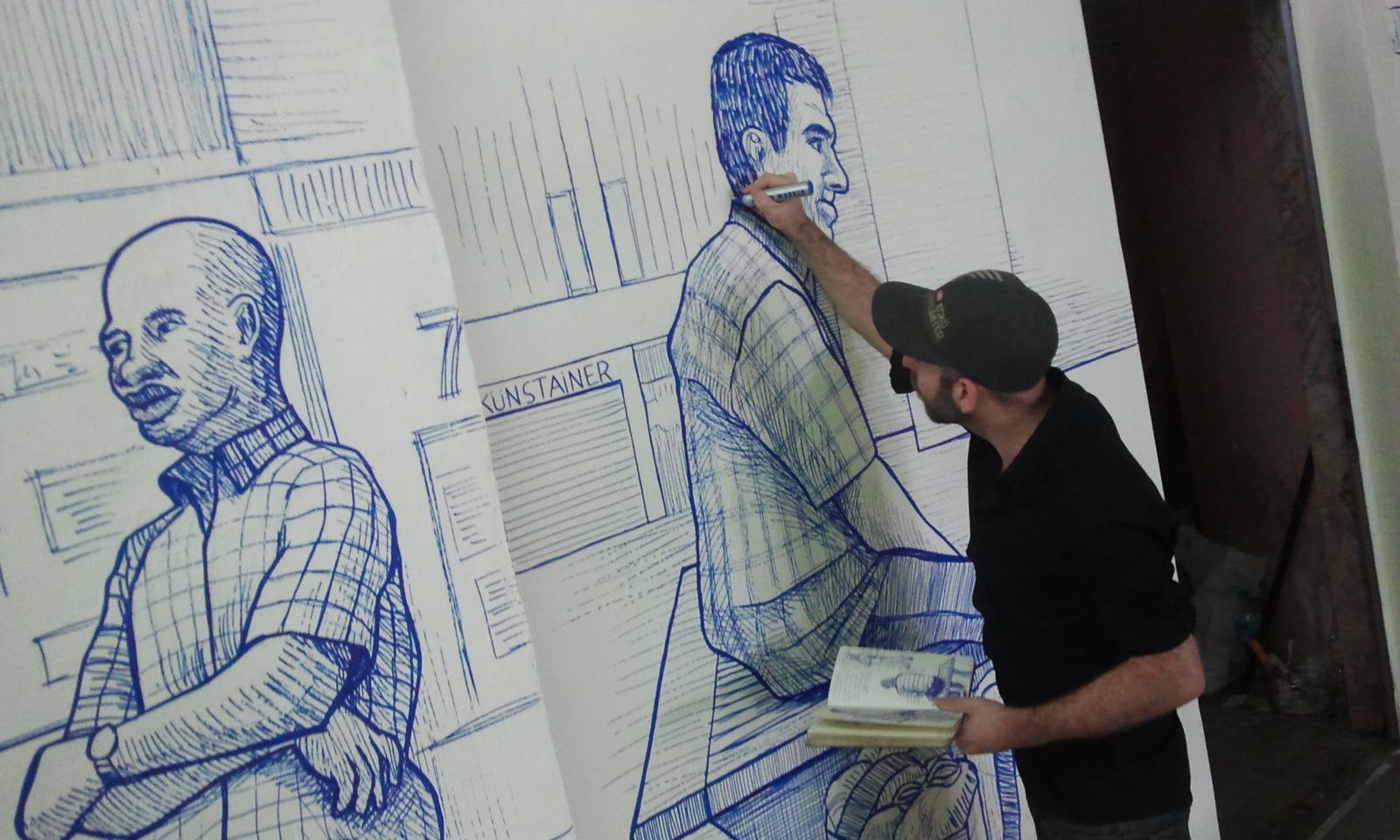 """Tziqui Artworks retocant una de les obres de la intervenció """"El que espera"""""""