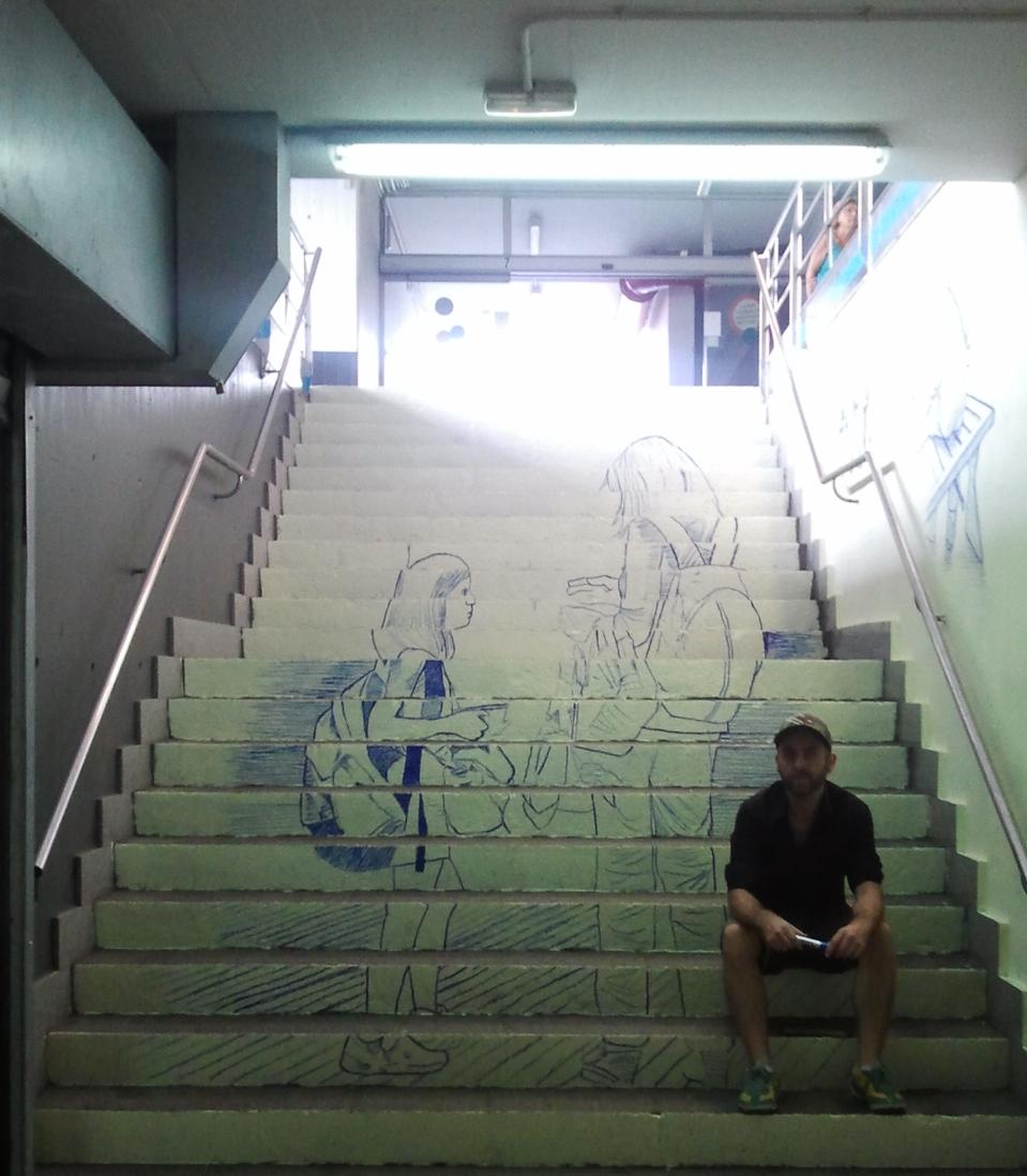 """Tziqui Artworks assegut a les escales de l'estació d'autobusos, al costat d'una de les anamorfosi de la intervenció artística """"El que espera"""""""