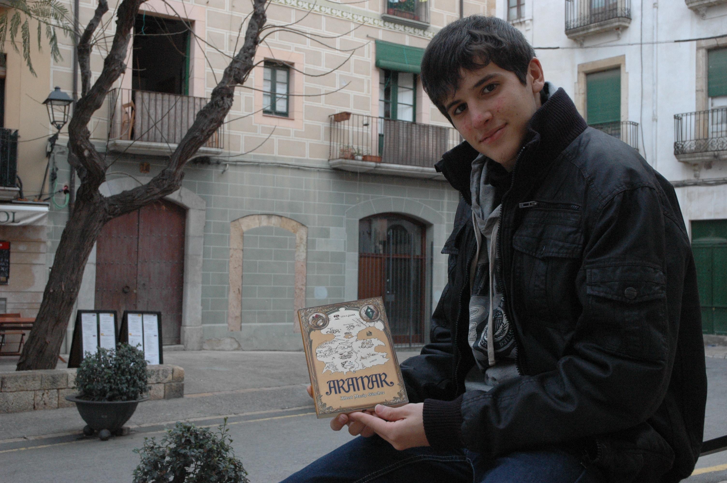 El jove Albert Masip sosté la portada del seu primer llibre, 'Aramar'